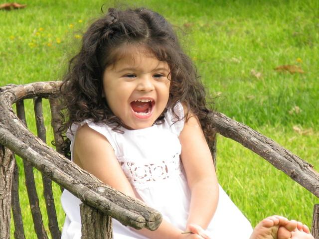 černovlasá holčička sedící v dřevěném křesílku venku